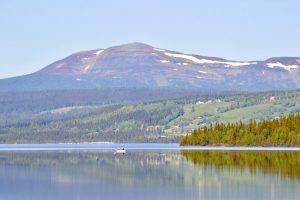 Sommaridyll med fiske på den spegelblanka Åkersjön. Byn Åkersjön och fjället Ansätten i bakgrunden. Foto © flyttatillfjallen.se